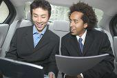 Two businessmen working in backseat