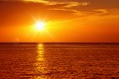 Colorful empty seascape with shiny sea over cloudy sky and sun during sunset in Cozumel, Mexico poster