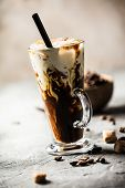 Iced Coffee In A Tall Glass With Cream Poured Over poster