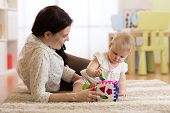 Woman And Baby Girl Playing With Developmental Toys In Nursery. Kid Learning Colors, Sizes And Shape poster
