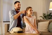 family and people concept - happy father braiding daughter hair at home in evening poster