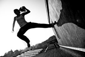 pic of parkour  - Monochrome image of a female traceur using momentume and speed to propel herself through the air between two buildings while participating in parkour - JPG