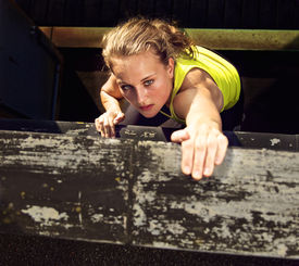foto of parkour  - Determination on the face of a traceur climbing the wall of a high industrial building while demonstrating parkour - JPG