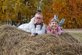 Two girl lying on a haystack