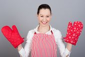 Funny housewife woman with oven mittens and red apron isolated on gray background.