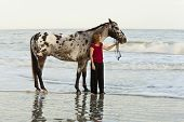 woman on beach with appaloosa horse, time exposure with wave motion