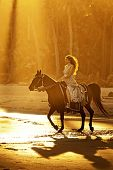 image of bareback  - backlit woman on horseback in formal dress riding on beach - JPG