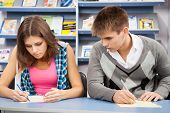Estudiante hacer trampas en el examen, mirando la escritura de un amigo