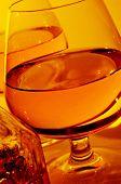 closeup of some cognac glasses with liquor and a vintage glass liquor bottle