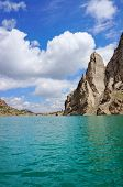 Grandiose rocks and Kelsu mountain lake against the background of colourful dark blue sky with cloud