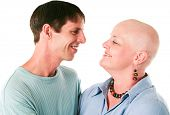 Cancer patient smiles at her loving, supportive husband.  White background.