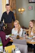Young female friends with food on table while waiter holding menu at cafe