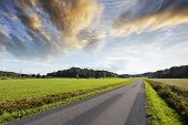small lonely country-road, sunset clouds and summer landscape