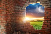 stock photo of green wall  - Broken bricks wall and landscape - JPG