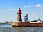 red lighthouse at the harbor entrance of Bremerhaven, modern buildings in background