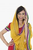 stock photo of salwar  - Beautiful Indian woman in traditional wear answering phone call over white background - JPG
