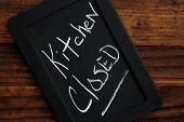 Miniature blackboard  - with 'kitchen closed' message handwritten in chalk - on rustic dark wood background.  Humorous sign for when the cook needs a break.