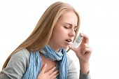 stock photo of inhalant  - Young woman using an asthma inhaler as prevention - JPG