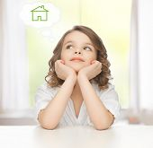 family and new home concept - pre-teen girl dreaming about the house