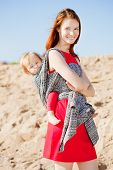 Beauty woman with a baby in a sling. Mom and baby. Mother and child.