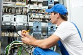 stock photo of engineer  - Young adult electrician builder engineer inspecting electric counter equipment in distribution fuse box - JPG