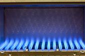 Blue flames of a gas burner inside of a boiler