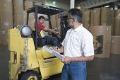 Supervisor looking at man in forklift truck at newspaper factory