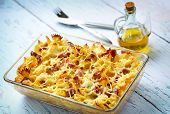 Baked pasta with smoked meat, drizzled with olive oil