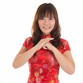 Asian woman with Chinese traditional dress cheongsam or qipao greeting. Chinese new year concept, fe