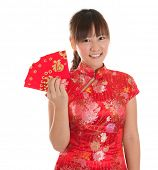 Pretty Asian girl with Chinese traditional dress cheongsam or qipao holding ang pow or red packet mo