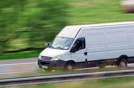 stock photo of moving van  - Very fast driving white van delivering goods - JPG
