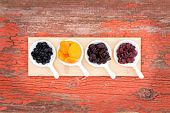 stock photo of apricot  - Overhead view of a display on rustic grunge wood of assorted dried berries and fruit in ceramic ramekins with golden apricots cherries blueberries and cranberries for a healthy snack or appetizer - JPG