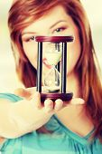 Teen woman holding hourglass