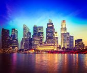 Vintage retro hipster style travel image of Singapore skyline and river in evening