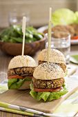 stock photo of veggie burger  - Vegan burgers with  beans and vegetables served in a poppy seed bun - JPG