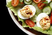 Closeup view of a salad of deviled eggs served with lettuce, miniature tomatoes, sliced cucumber and chopped green onions or scallions, from above over a black background