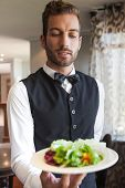 Waiter showing bowl of salad to camera in a fancy restaurant