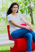Beautiful Teen Girl Sitting Outdoors On Red Chair