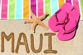 Maui, Hawaii beach travel concept. Maui written in sand with water next to beach towel, summer sandals and starfish. Hawaiian vacation holidays