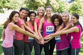 image of breast  - Portrait of female breast cancer marathon runners stacking hands in park - JPG