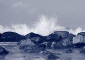 Black Rocks Protecting Coast Against Crashing White Waves