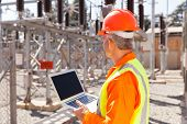 stock photo of substation  - senior technician holding laptop computer in substation - JPG