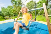 Smiling boy and girl swing in opposite directions