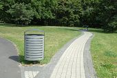 stock photo of dust-bin  - Grey metal dust bin nearby pavement in park in Poznan Poland - JPG