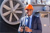 handsome african electrical manager with binoculars visiting substation