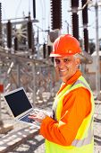 smiling senior electrician using laptop in substation