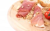 Composition of prosciutto on wooden platter.
