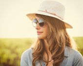 Fashion portrait of beautiful young woman in hat and sunglasses oustide, bright warm sunny color ton