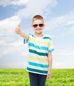 happiness, summer, childhood, gesture and people concept - smiling cute little boy in sunglasses ove