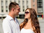 love, travel, tourism, people and friendship concept - smiling couple wearing sunglasses looking at